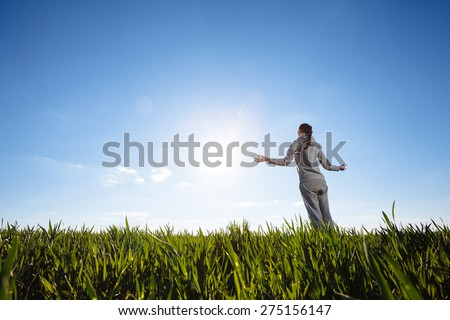 Teenage girl enjoy with sunshine in grass field and doing yoga - stock photo