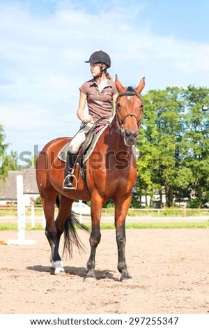Teenage girl equestrian riding thoroughbred horseback. Vibrant summertime outdoors image. - stock photo