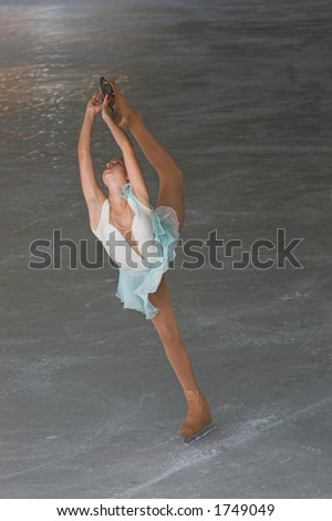 Teenage girl figure skating performance doeing a Bielmann. - stock photo
