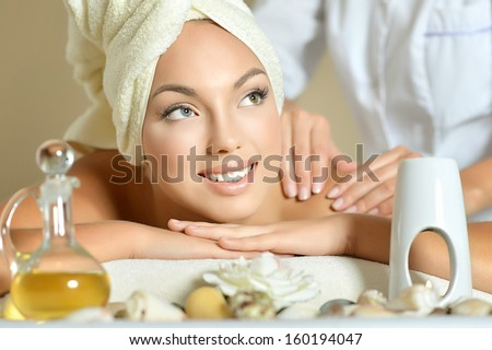 Teenage girl getting facial massage in spa - stock photo