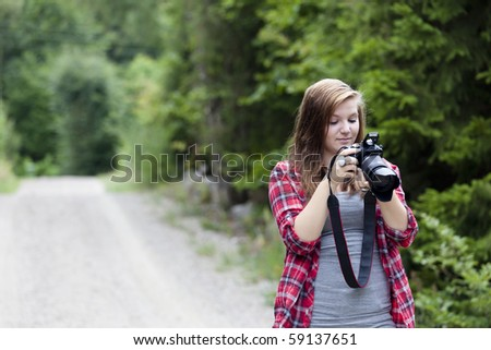 Teenage girl holding a camera shooting a picture outdoors. She is looking at the back of the camera - stock photo