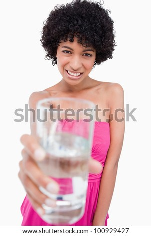 Teenage girl holding a glass of water in front of her while showing a great smile - stock photo