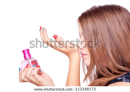 Teenage girl holding perfume and smelling perfumed hand, isolated on white - stock photo
