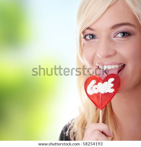 Teenage girl holding red heart shaped lollipop - stock photo