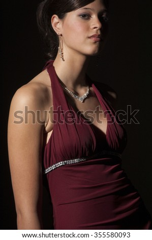 Teenage girl in a red evening gown with diamond necklace and earings, in the studio, dramatic lighting. - stock photo
