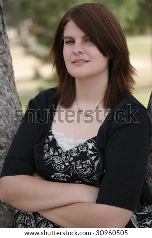 Teenage girl in dress with arms folded in a park - stock photo