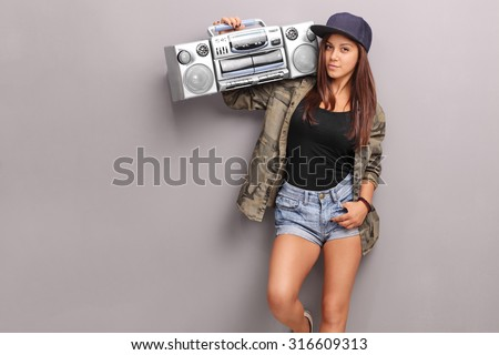 Teenage girl in hip hop clothes holding a ghetto blaster over her shoulder and looking at the camera - stock photo