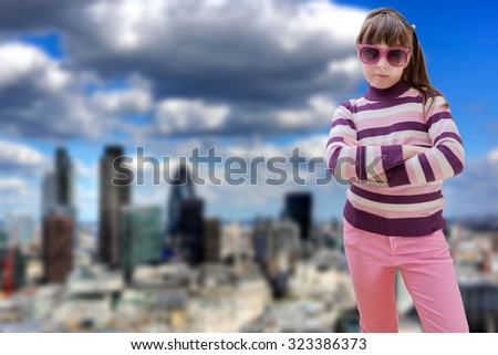 Teenage girl in pink wears sunglasses with modern city in background - stock photo