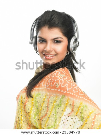 Teenage  girl in sari listening to music with head phones - stock photo