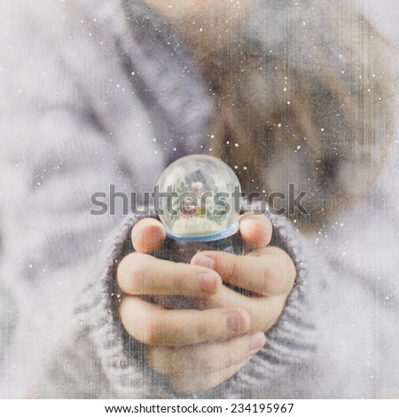 teenage girl in winter clothes with small snow globe - stock photo