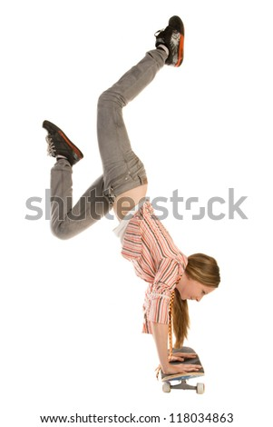 Teenage girl is doing handstand on skateboard, isolated on white background - stock photo