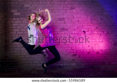 Teenage girl jump in the air against brick wall urban style lit with flash - stock photo