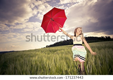 teenage girl jumping with an umbrella in front of rural landscape - stock photo