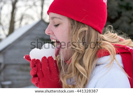 teenage girl licking an ice heart in red gloves - stock photo