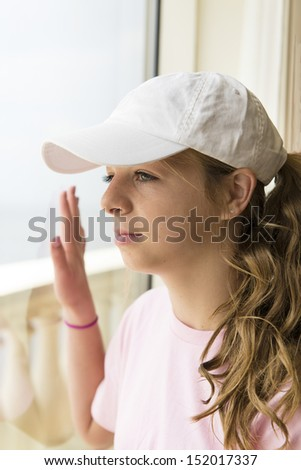 Teenage girl looking out resort window on vacation - stock photo