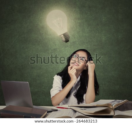 Teenage girl looking up at light bulb while studying with textbooks and laptop in the class - stock photo