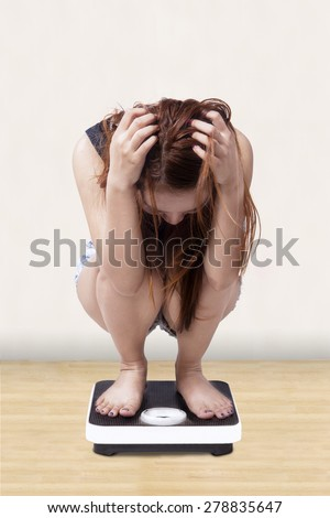 Teenage girl looks stressed when measure her weight on a weight scales at home - stock photo