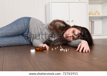 Teenage girl lying on the floor at home, alone with a blank expression on her face. - stock photo