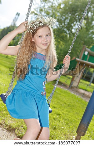teenage girl on a swing in the park - stock photo