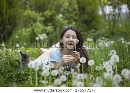 Teenage girl on the field with dandelions - stock photo