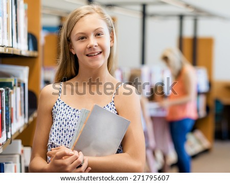 Teenage girl picking a book in public library - stock photo