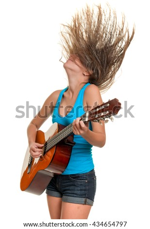 Teenage girl playing an acoustic guitar with her hair floating on the air- Isolated on a white background - stock photo