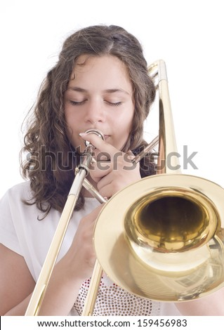 Teenage girl playing the trombone. Isolated on a white background. Studio shot - stock photo