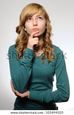 Teenage Girl Pondering. Teenage girl looking up with her hand on her chin as if she is thinking. Note: not isolated. - stock photo