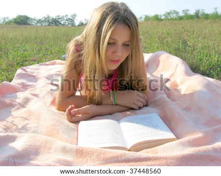 Teenage girl reading a book outdoor - stock photo