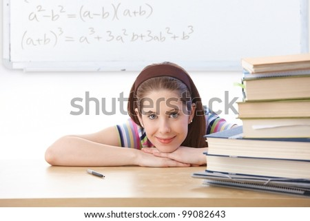Teenage girl sitting at desk in classroom front of whiteboard, smiling at camera. - stock photo