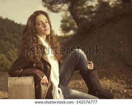 Teenage girl sitting on a fence - stock photo