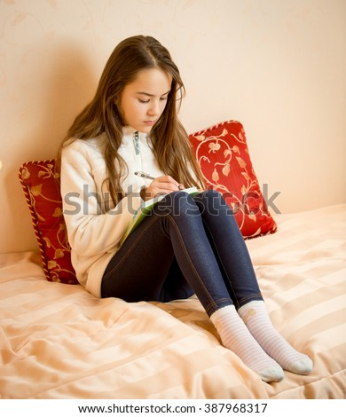 Teenage girl sitting on bed and writing poems in notebook - stock photo