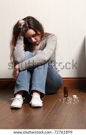 Teenage girl sitting on the floor at home, looking scared and frightened. - stock photo