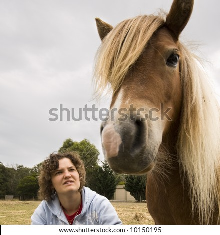 Teenage girl sitting on the ground looking at her pony - stock photo