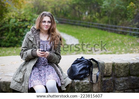 teenage girl sitting outside and looking at her phone - stock photo