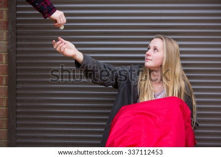 Teenage Girl Sleeping On The Street Being Given Money - stock photo
