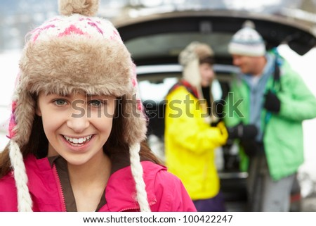 Teenage Girl Smiling At Camera Whilst Family Load Skis In Boot Of Car - stock photo