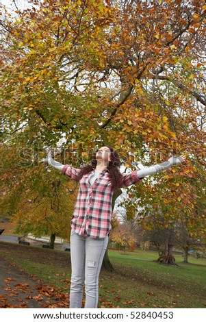 Teenage Girl Standing In Autumn Park With Arms Outstretched - stock photo