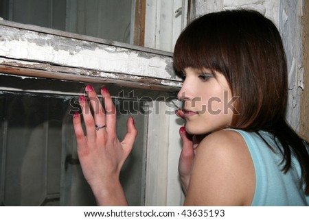 Teenage girl standing near old window - stock photo