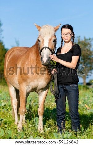 Teenage girl standing on a meadow in summer with her horse - stock photo
