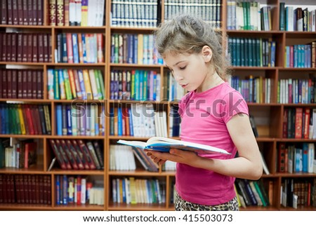 Teenage girl stands in library room with bookshelves reading book. - stock photo