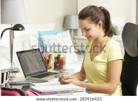 Teenage Girl Studying At Desk In Bedroom Using Mobile Phone - stock photo