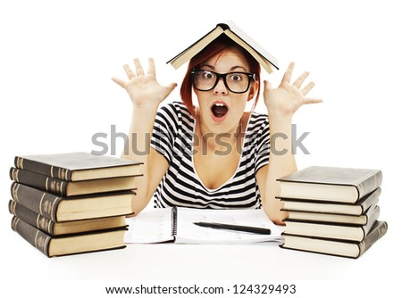 Teenage girl studying at the desk being shocked. Isolated on white background - stock photo