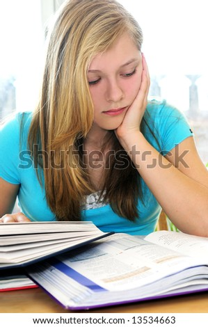 Teenage girl studying with textbooks looking unhappy - stock photo