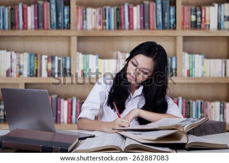 Teenage girl studying with textbooks while writing on a book in the library - stock photo