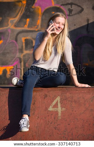 Teenage Girl Talking On Mobile Phone In Playground - stock photo