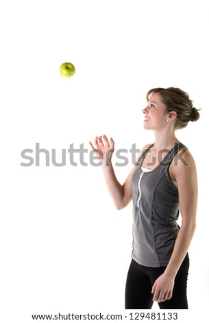 Teenage girl throwing an apple in the air. Isolated on white background - stock photo