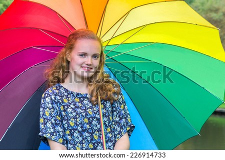 Teenage girl under colored umbrella outdoors - stock photo