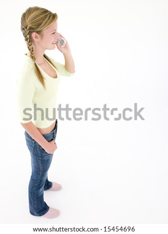 Teenage girl using cellular phone and smiling - stock photo