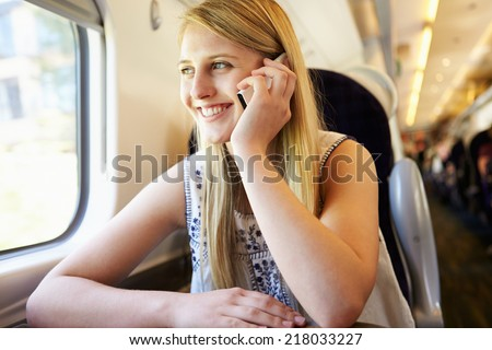 Teenage Girl Using Mobile Phone On Train Journey - stock photo